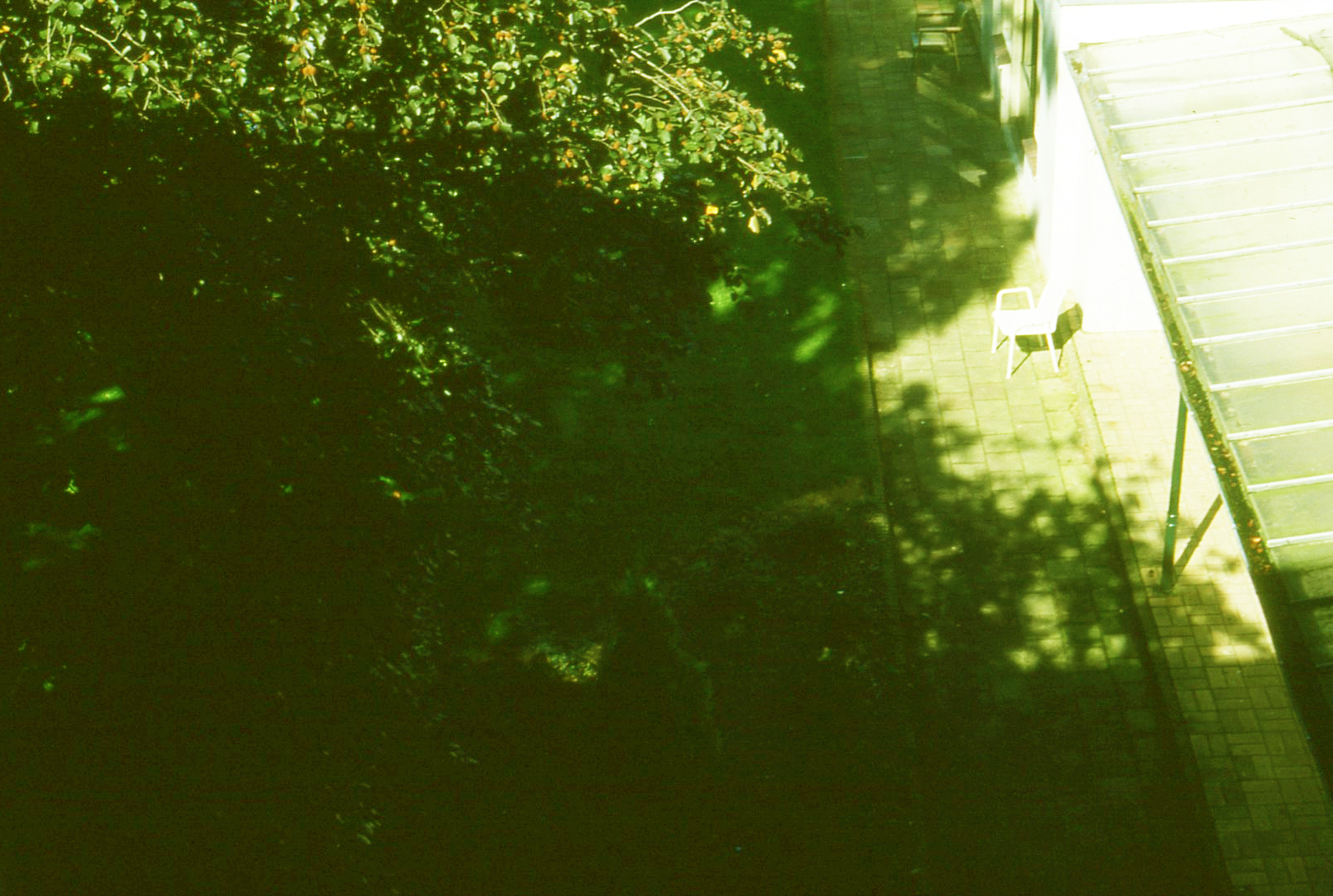 Grasveld op binnenplaats met een stoel, van bovenaf gezien.