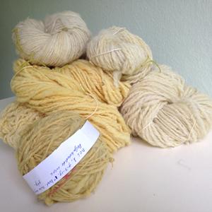 Gesponnen wol in strengen en een bol, geel en wit